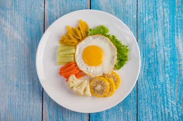 Café da manhã americano em uma mesa azul com ovo frito, salada, abóbora, pepino, cenoura, milho, couve-flor e tomate.