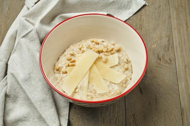 Café da manhã apetitoso e saudável - aveia com parmigiano, queijo parmesão em uma tigela sobre uma superfície de madeira. fechar-se. copie o espaço