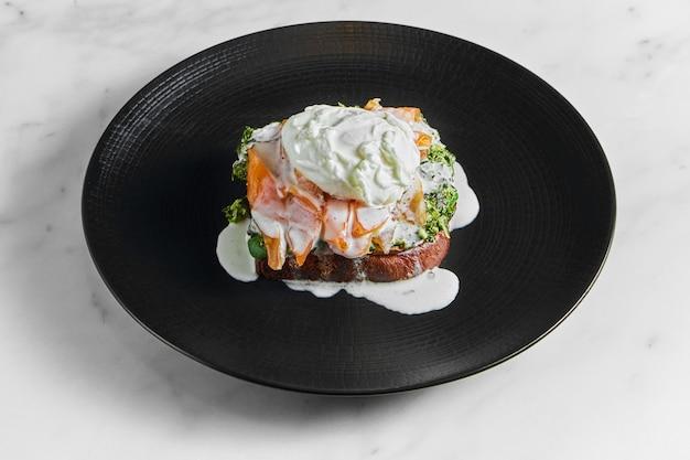 Café da manhã apetitoso e saudável - torradas com salmão, espinafre cremoso e ovo escalfado, servido em um prato preto sobre uma superfície de mármore