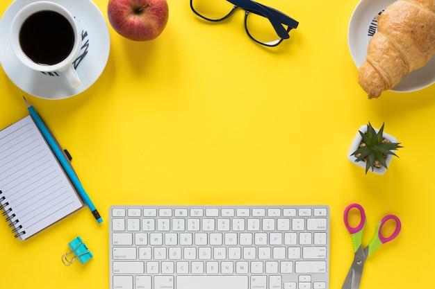 Café da manhã; artigos de papelaria de escritório e teclado em fundo amarelo para escrever o texto