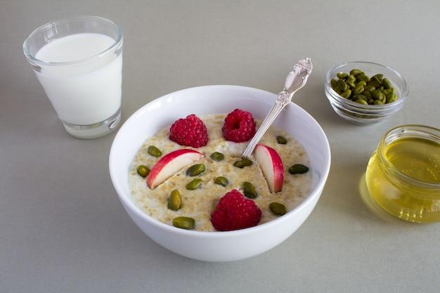 Café da manhã: aveia com maçã, framboesa, mel, nozes e leite no copo no fundo cinza