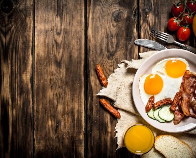 Café da manhã bacon frito com ovos e suco de laranja em uma mesa de madeira