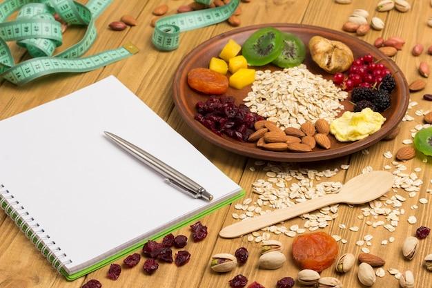 Café da manhã balanceado de muesli. frutas, sementes de bagas, comida vegetariana de proteína de nozes. plano de dieta saudável. fita métrica, caderno, caneta em fundo de madeira