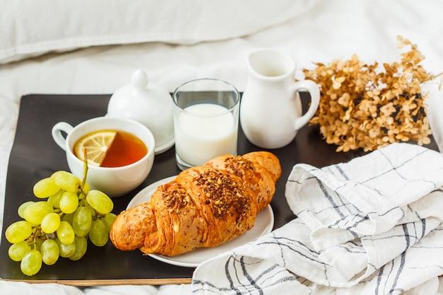 Café da manhã bonito com um croissant e chá em uma bandeja preta na cama.