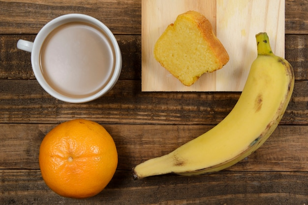 Café da manhã brasileiro com café com leite, bolo de milho, banana e tangerina