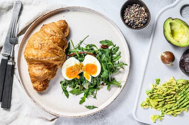 Café da manhã, brunch com abacate, rúcula, croissant e ovo