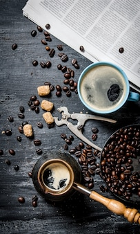 Café da manhã. bule de café e um jornal com grãos de café torrados na mesa de madeira.
