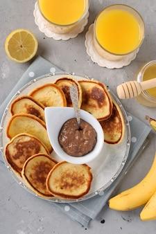 Café da manhã caseiro: panquecas com geleia de chocolate, mel, bananas e suco de laranja em guardanapo cinza sobre fundo de concreto, vista de cima, formato vertical