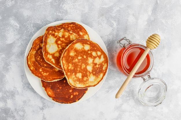 Café da manhã caseiro: panquecas de estilo americano, servidas com peras e mel com uma xícara de chá no concreto. vista superior e cópia