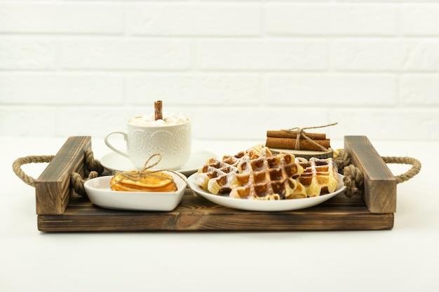 Café da manhã cedo, café com marshmallows e um pedaço de canela e waffles belgas em uma bandeja de madeira