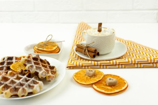 Café da manhã cedo, café com marshmallows e um pedaço de canela e waffles belgas