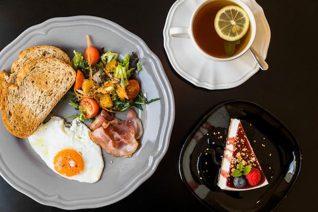 Café da manhã; chá de limão; cheesecake de frutas o fundo preto
