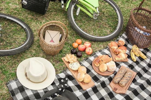 Café da manhã; chapéu; cesta e bicicleta no piquenique no parque
