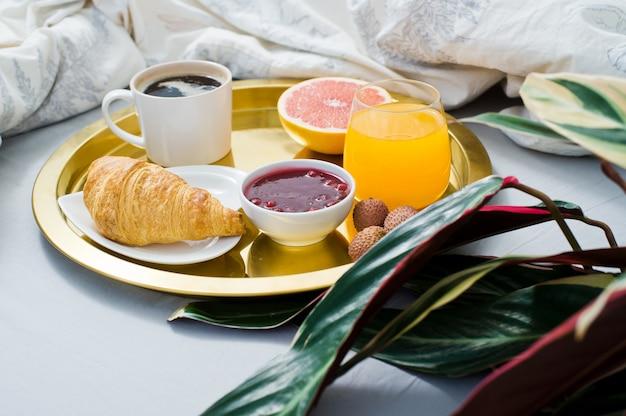 Café da manhã clássico na cama, serviço de hotel. café, geléia, croissant, suco de laranja, grapefruit, lichia.