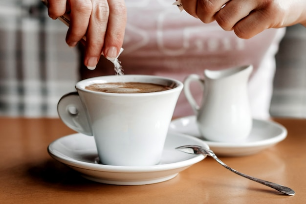 Café da manhã. close up das mãos das mulheres com copo de café em um café. femininas, mãos, segurando, xícaras café, ligado, um, tabela madeira, em, um, café, cor vintage, tom