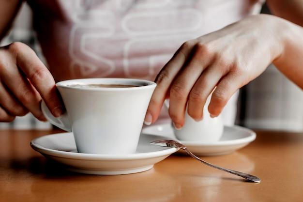 Café da manhã. close up das mãos das mulheres com copo de café em um café.