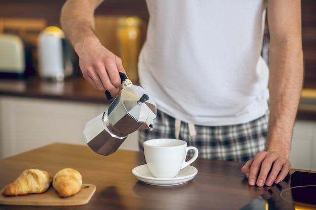 Café da manhã. close-up de um homem em trajes caseiros servindo café na xícara