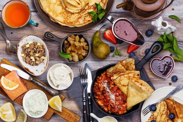 Café da manhã colorido, saboroso e saboroso com crepes e diferentes recheios e molhos