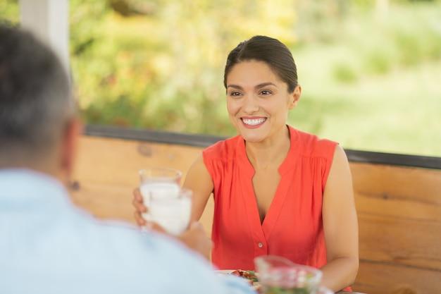 Café da manhã com a amada. esposa radiante de olhos escuros sorrindo enquanto toma café da manhã com a amada