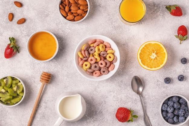 Café da manhã com anéis coloridos de cereais, frutas, leite, suco