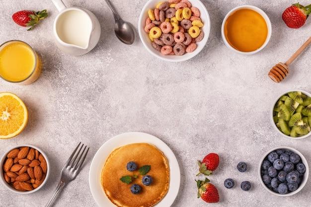 Café da manhã com anéis de cereais coloridos, panquecas, frutas, leite, suco
