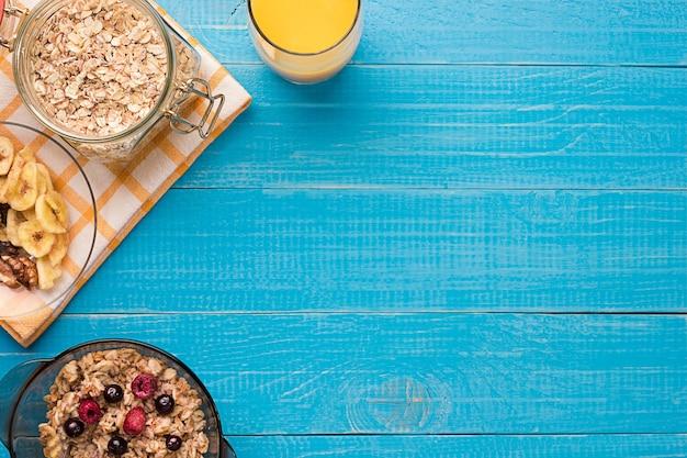 Café da manhã com aveia e frutas na tigela e suco de laranja na xícara. vista do topo. ainda vida. espaço para texto.