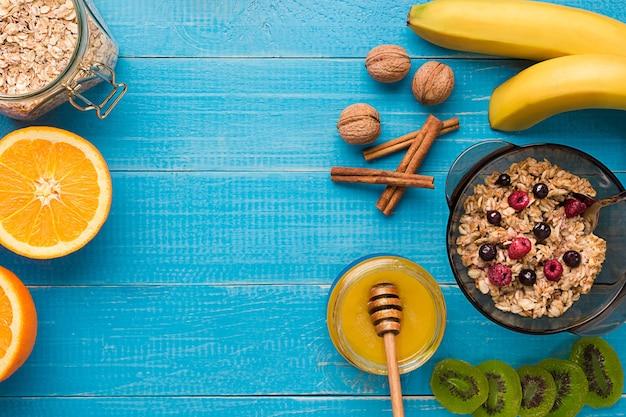 Café da manhã com aveia, frutas vermelhas, mel, frutas e nozes. vista do topo. ainda, vida, espaço para texto.