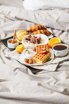Café da manhã com aveia, waffles, café, croissants e frutas na cama.