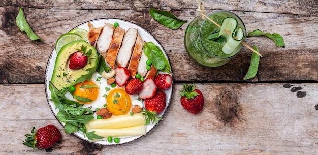 Café da manhã com baixo teor de carboidratos e alto teor de gordura, filé de frango grelhado e abacate, ovos fritos com morango, queijo e nozes. smoothie desintoxicante, verde fresco, dieta cetogênica. conceito de comida saudável, vista de cima,
