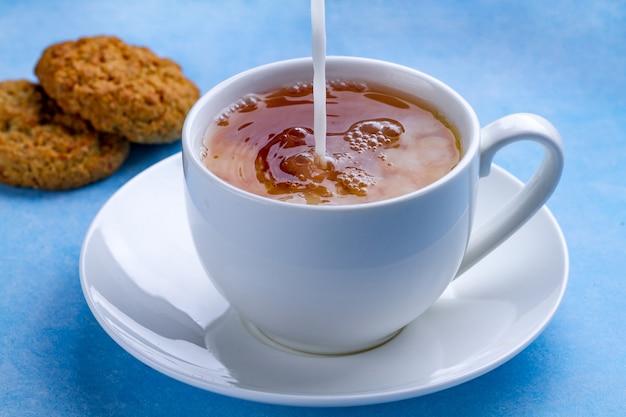 Café da manhã com biscoitos de aveia e derramar leite em uma xícara de chá preto. farinha, sobremesa de cereais e bebida quente