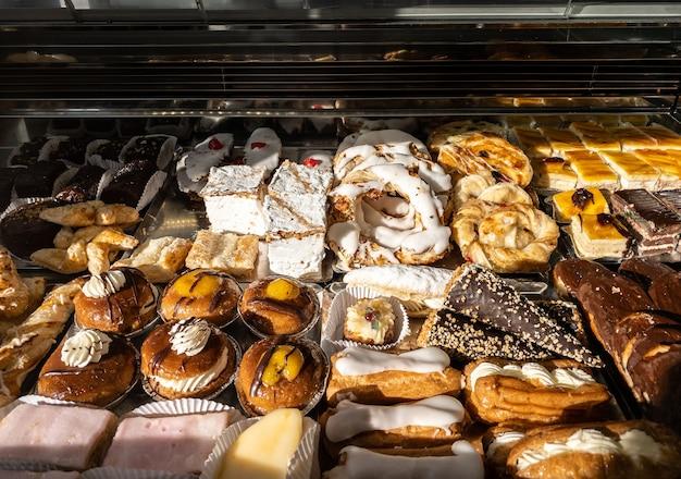 Café da manhã com biscoitos espanhóis, pastéis doces, massa folhada, açúcar de confeiteiro e sobremesa de maçãs assadas. doçaria típica consumida na vitrine de uma confeitaria na espanha.