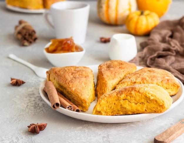 Café da manhã com bolinhos de abóbora picantes, uma xícara de chá e leite.