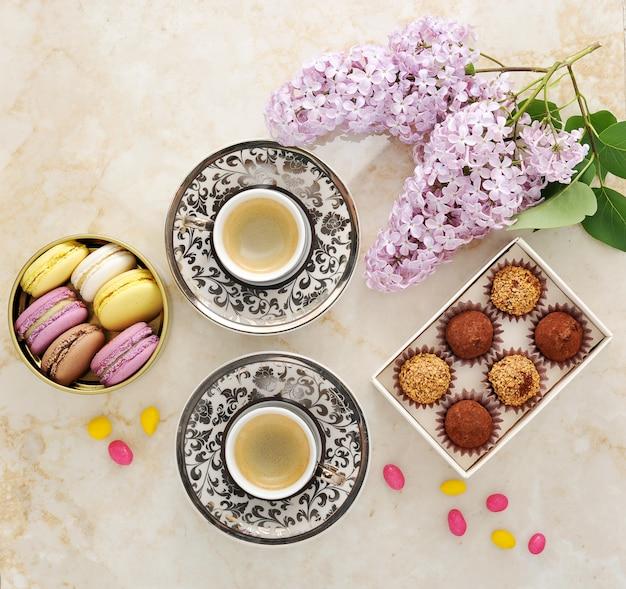Café da manhã com bolos macarons e um ramo de lilás