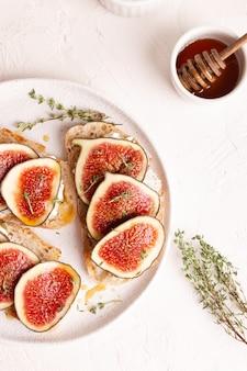 Café da manhã com bruschettas doces com figos e mel em prato branco