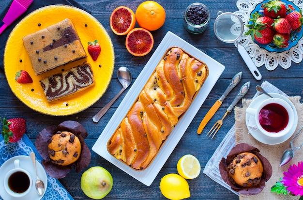Café da manhã com café e chá com diferentes bolos e frutas em uma mesa de madeira