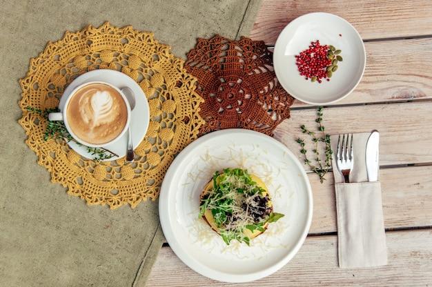 Café da manhã com café e sanduíche na mesa de madeira com garfo e faca