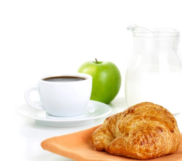 Café da manhã com café, leite, croissant e maçã verde isolada no branco
