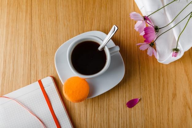 Café da manhã com café, macaron colorido e diário aberto