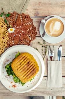 Café da manhã com cappuccino e sanduíche na mesa de madeira com garfo e faca