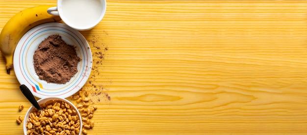 Café da manhã com cereais em uma tigela com leite, cacau e banana sobre um fundo claro de madeira