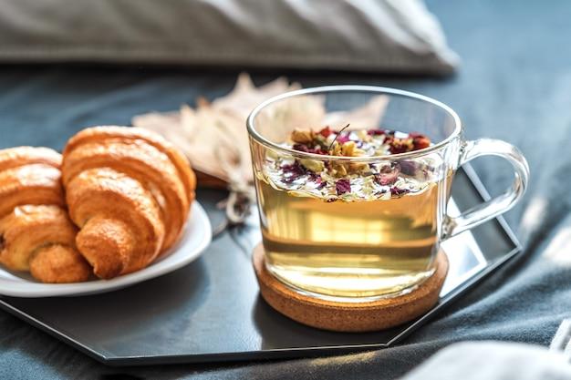 Café da manhã com chá de ervas e croissants na cama com lençóis cinza em uma sala ensolarada