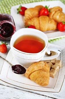 Café da manhã com chá, geléia e croissants frescos em madeira