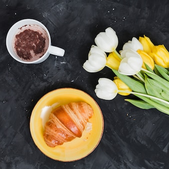 Café da manhã com croissant e flores