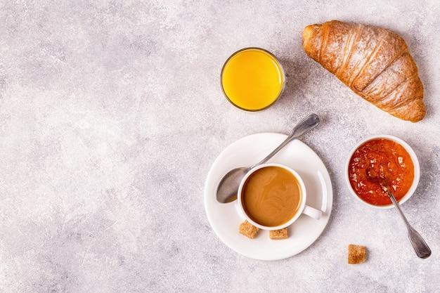 Café da manhã com croissant fresco, suco de laranja e café