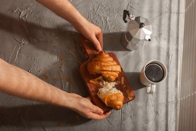 Café da manhã com croissant na tábua e café preto, refeição matinal e conceito de café da manhã