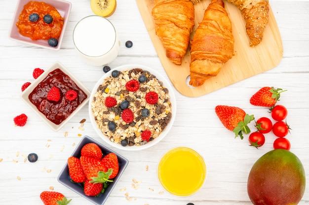 Café da manhã com croissants de manteiga e flocos de milho, cereais e passas.