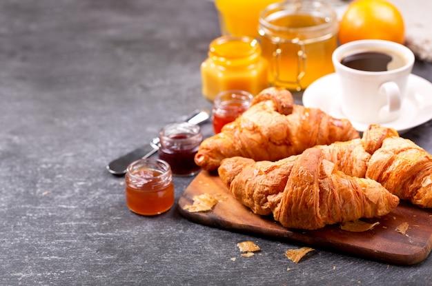 Café da manhã com croissants frescos e café na mesa escura
