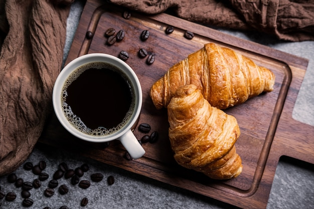 Café da manhã com croissants frescos e xícara de café preto na placa de madeira