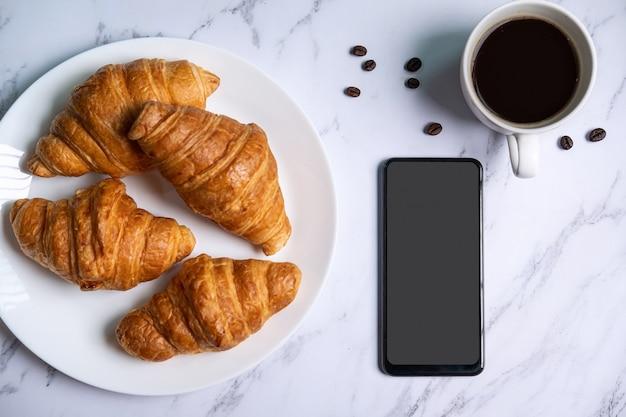 Café da manhã com croissants frescos e xícara de café preto, telefone inteligente de tela vazia, vista superior