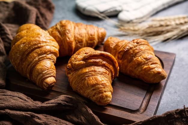 Café da manhã com croissants frescos na placa de madeira